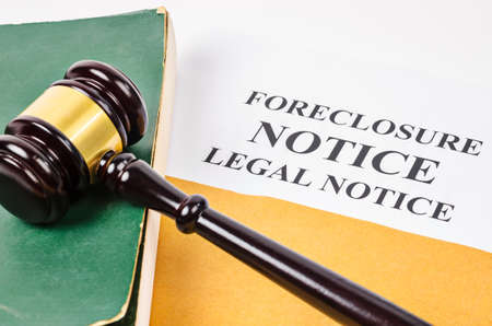 Gavel and Foreclosure Notice document with old book. Foto de archivo