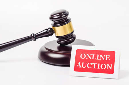 Online auction concept with wooden gavel on white background.