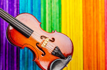 Violin on colorful wooden background.