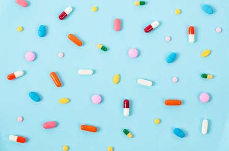 青の背景にカラフルな錠剤の錠剤。