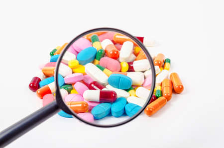 pills under magnifying glass on white background.