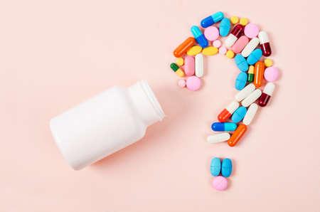 Pillen of capsules als vraagteken en witte plastic fles.
