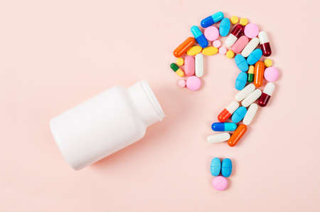 Pills or capsules as a question mark and white plastic bottle. Imagens