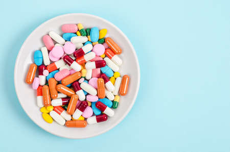 A top view of colourful medicine pills and capsules in white plate on blue background. Copy space for the ads. Stockfoto