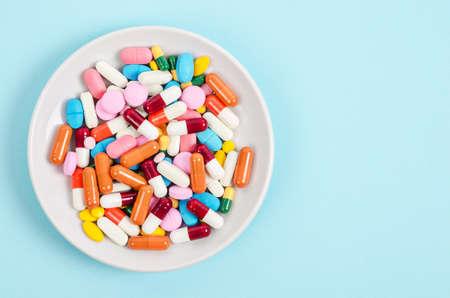 Odgórny widok kolorowe medycyn kapsuły w bielu talerzu na błękitnym tle i pigułki. Skopiuj miejsce na reklamy.