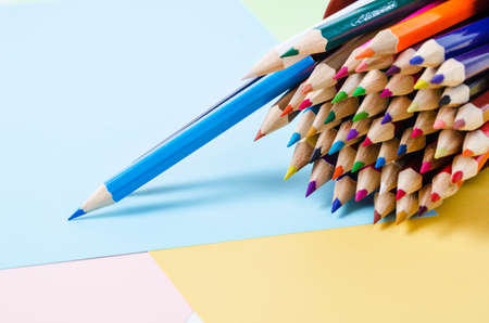 Wooden color pencils on color paper.