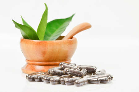 Natural medicine capsule pill with black herb, and wooden mortar on white background for alternative medical concept. Stock Photo