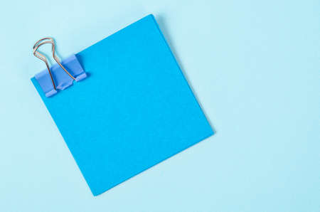 Blue binder clips and blue sticky notes on blue background. Stock Photo