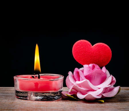 Red Candle Burning with red heart and pink rose. Valentine concept.
