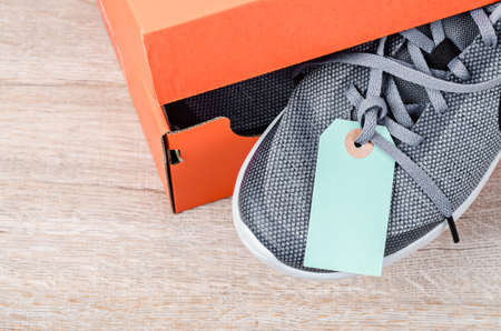 New blue sneakers with blank paper tag in paper box on wooden