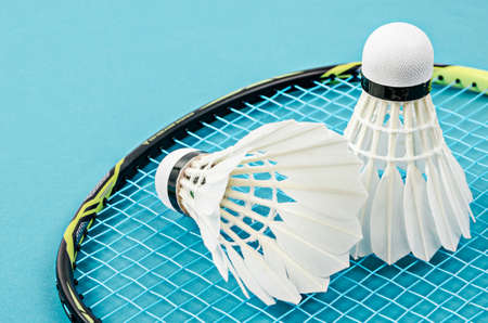 Close up shuttlecock and badminton racket on blue Stok Fotoğraf