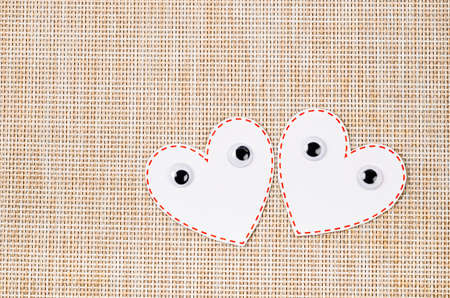 White heart paper with eyes on wooden mat background. Valentine concept. 스톡 콘텐츠