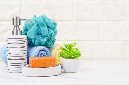 Jabón de hierbas, esponja de ducha y botella de bomba de champú dentro de un fondo de baño brillante.