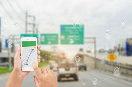 female hands holding a smart phone showing part of navigator map over screen on connection line over the road, Navigation concept. Imagens