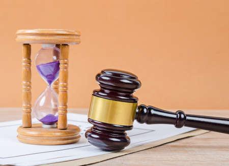 Martillo del juez con reloj de arena en el fondo de la mesa.