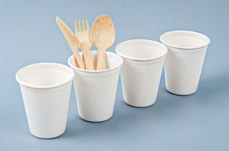 Water glass made from plant fiber and disposable spoon. Natural fiber eco food and drink packaging concept. Stock Photo