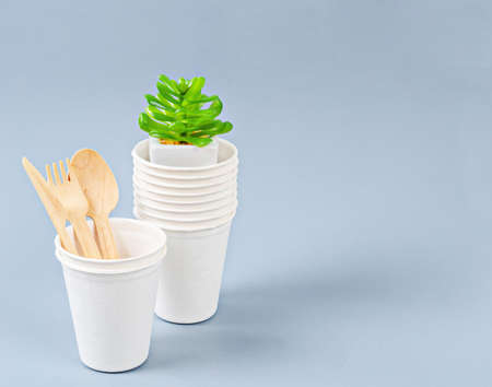 Biodegradable glass of water and disposable wooden spoon. Eco friendly concept.