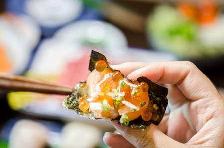 Main tenant le sashimi de saumon avec feuille d'algues séchées au restaurant de cuisine japonaise. Banque d'images
