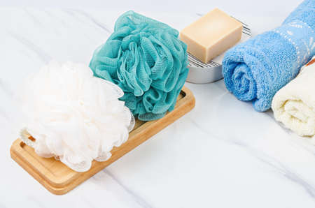 Shower sponge and herb soap inside a bright bathroom background.
