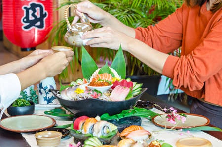 Close up women enjoy eating sashimi Japanese food in restaurant.