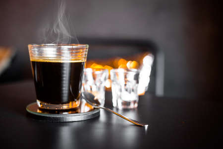 A cup of hot coffee with smoke in coffee shop.