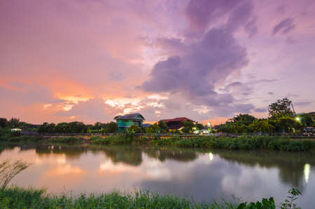Sunset on twilight with wooden house near river in Thailand.