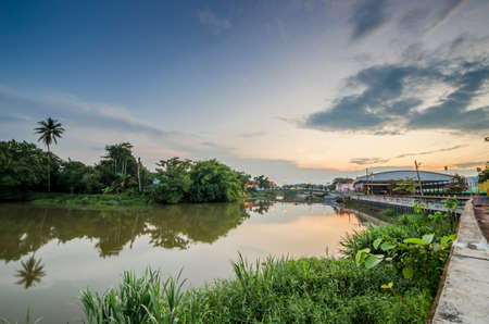 Bridge over the river with green forest after sunset time in Thailand.