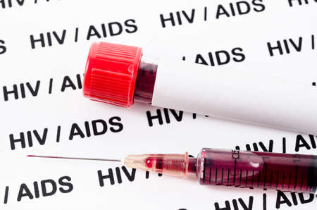 Sample blood for HIV test in syringe on HIV/AIDS background.