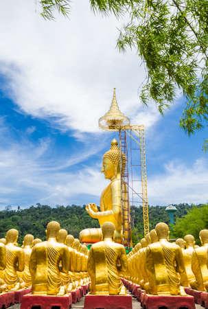 Row of disciple statues surrounding big buddha statue