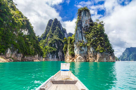 Wooden Thai traditional long-tail boat on a lake with mountains at Ratchaprapha Dam or Khao Sok National Park, Surat Thani Province, Thailand Banque d'images