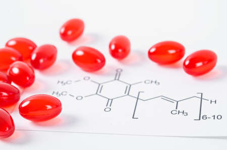 Vitamin Coenzyme Q10 with chemical formula on a white background. To prevent aging. Pills and medicine