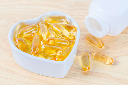 Fish oil capsules in wooden spoon with bottle on wooden background.