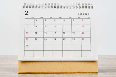 February 2021 Calendar desk for organizer to plan and reminder on wooden table.