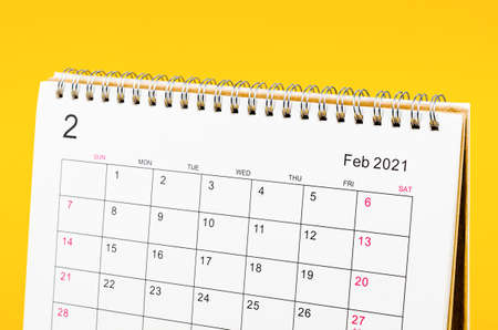 Close up February 2021 Calendar desk for organizer to plan and reminder on yellow background.