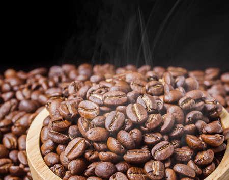 Coffee beans fresh roast with smoke on black background.