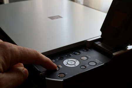 Finger pressing key on printer keypad  photo