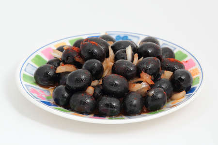a plate  of black olives marinated with onions and peppers photo