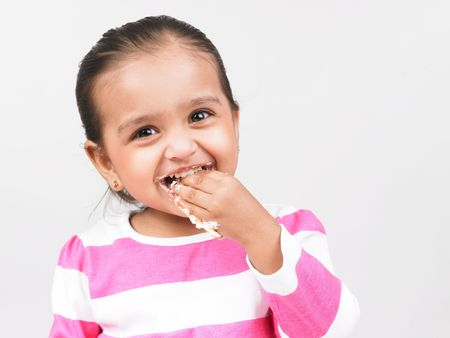 licking finger: asian girl eating Stock Photo