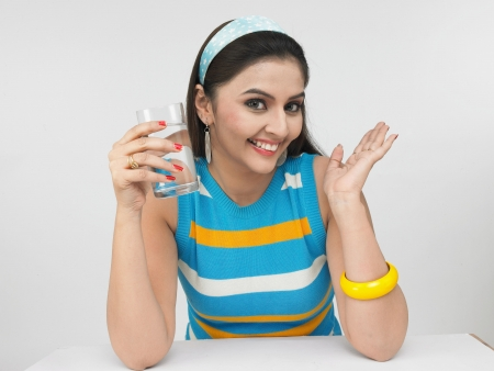 a sexy asian woman of indian origin drinking a glass of water