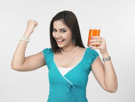 long nail: Una bella asiatica donna di origine indiana che beve succo d'arancia Archivio Fotografico