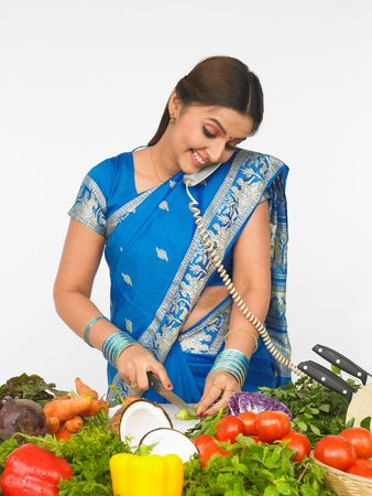 asian woman cutting vegetables and talking in the phone photo
