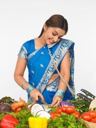 Asiatische Frau schneiden Gemüse und sprechen in das Telefon Standard-Bild