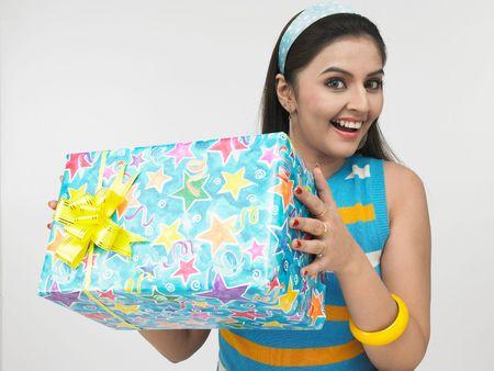 gifting: una linda chica asi�tico de origen indio con una caja de regalo
