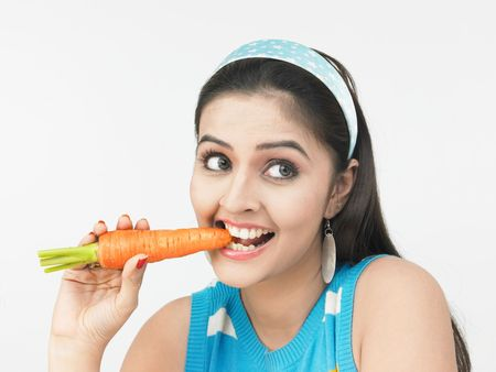 asian woman eating a carrot