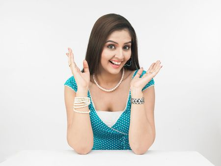 a surprised asian woman of indian origin shot in white background photo