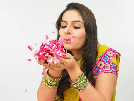 asian woman blowing rose petals held in her plam photo