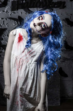 Little blue hair girl in bloody dress with scary halloween makeup Stock Photo