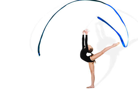 Yong gymnast performing exercise with ribbon on isolated background