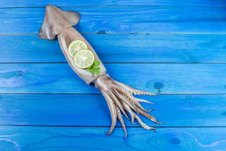 calamar fresco con limón y perejil. Whiteraw calamar mariscos o calamar fresco a la venta en el mercado húmedo para cocinar en mariscos u otro menú sobre fondo de madera azul desde la vista superior