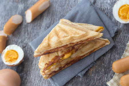 Pressed and toasted double panini with ham and cheese served on sandwich paper on a wooden table,egg,Hot dog
